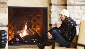 Woman sitting fireside drinking hot beverage at luxury resort